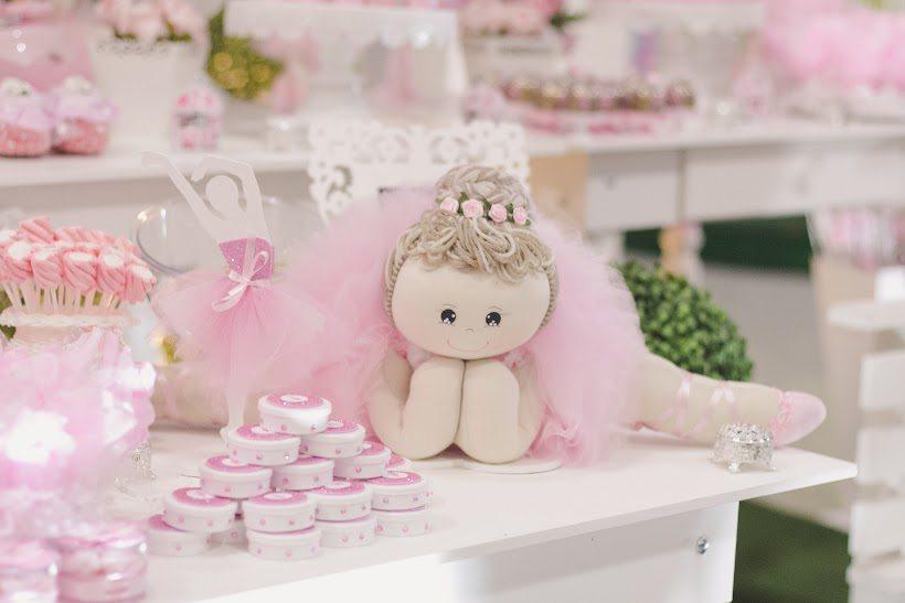 Mesa branca com doces decorados na cor rosa, uma boneca de pano à direita e uma planta na cor verde na ponta direita