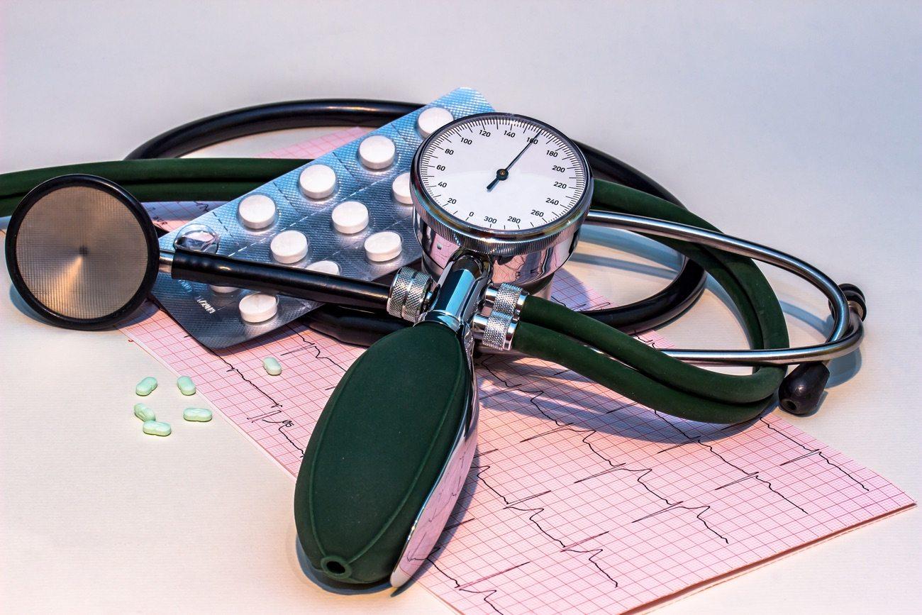 Ácido fólico na gestação. Na imagem há um medidor de pressão manual, um estetoscópio, ambos na cor preta. Embaixo, uma folha rosa escrita em preto e uma cartela de remédios.
