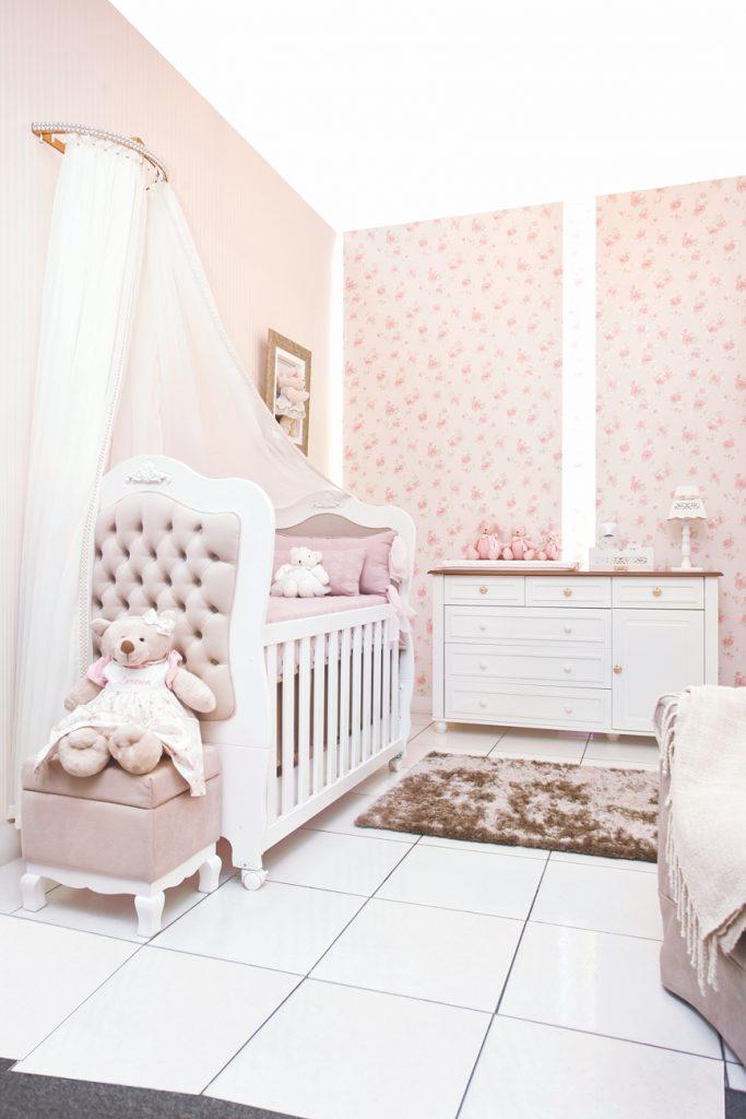 Quarto estilo romântico com berço branco com cabeceira capitonada em rosa. A frente, pufe quadrado rosa com ursinho de pelúcia rosa em cima. Ao fundo, um quadro na parede, que possui papel de parede rosa estampado. Além de uma cômoda branca com puxadores em formato de coroa. Em cima da cômoda, abajur branco, kit higiene também branco e ursinhos rosa.