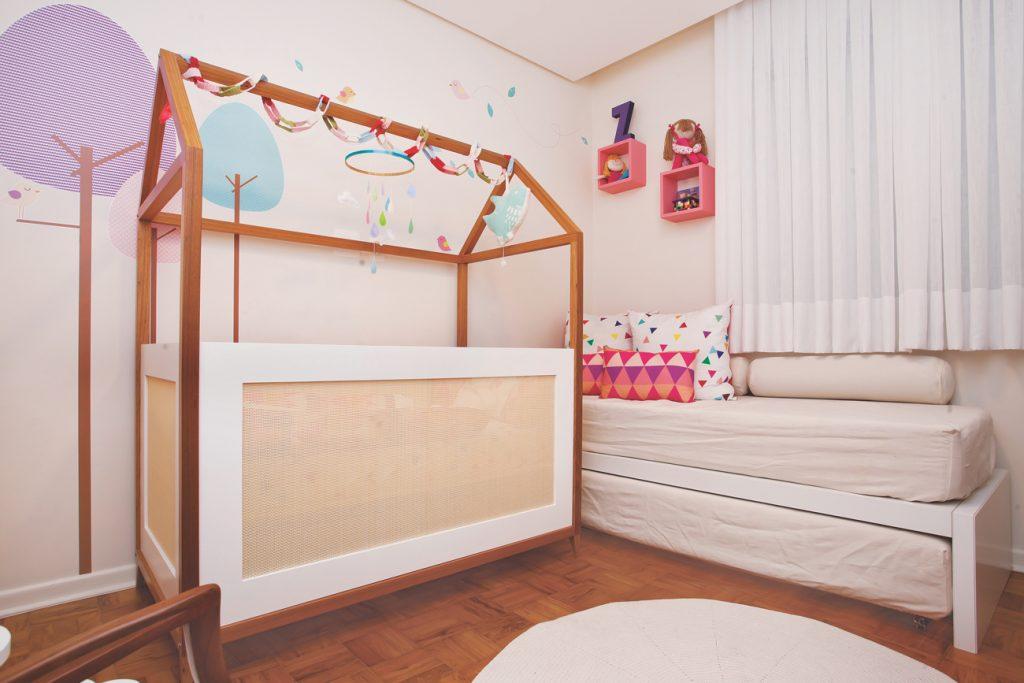 Quarto funcional com chão de madeira. Um berço em forma de casinha com estruturas de madeira e detalhes brancos em volta. Ao lado, uma cama branca com colchão bege. Na parede uma cortina branca e ao lado dois nichos cor-de-rosa. Logo acima dos nichos uma boneca e uma réplica da letra Z.