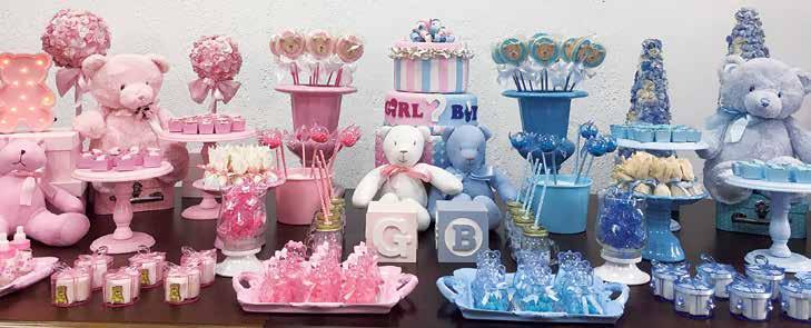 Mesa de madeira com diversos doces e bichos de pelúcia. Do lado esquerdo, os elementos são rosa. Do lado direito, os elementos são azuis.