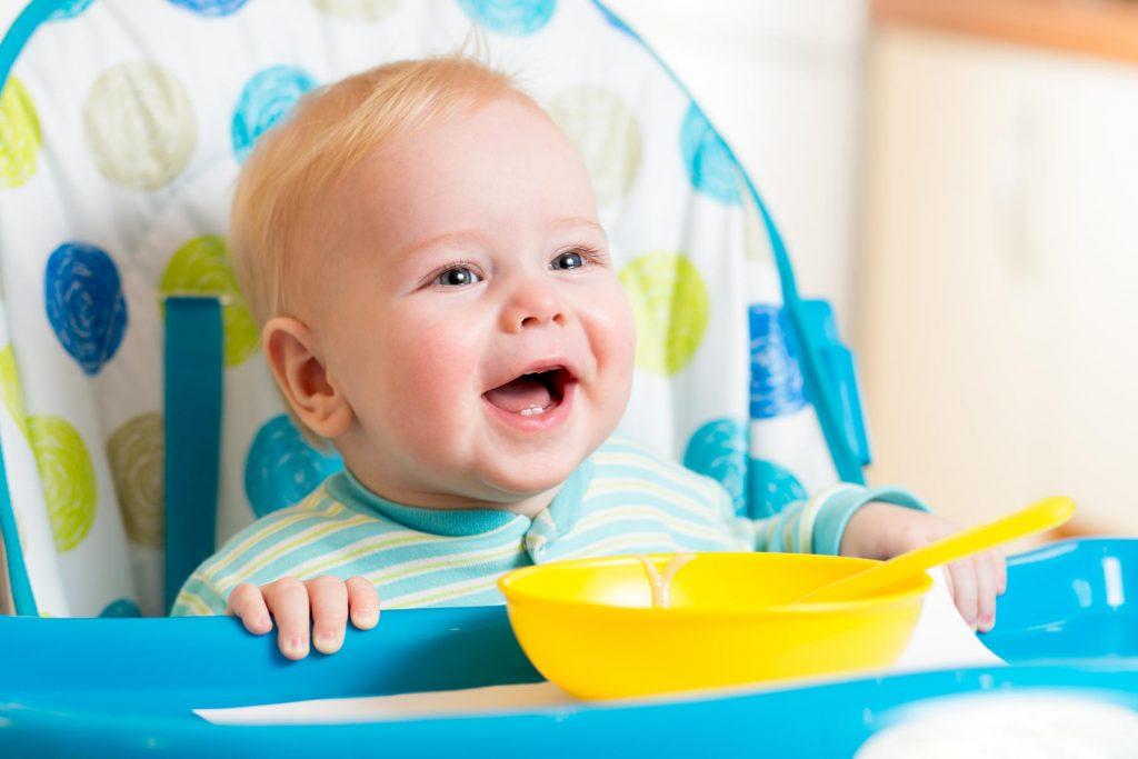 Bebê loiro sentado em um cadeirão branco com estampas azuis e verdes., Ele come em um prato amarelo