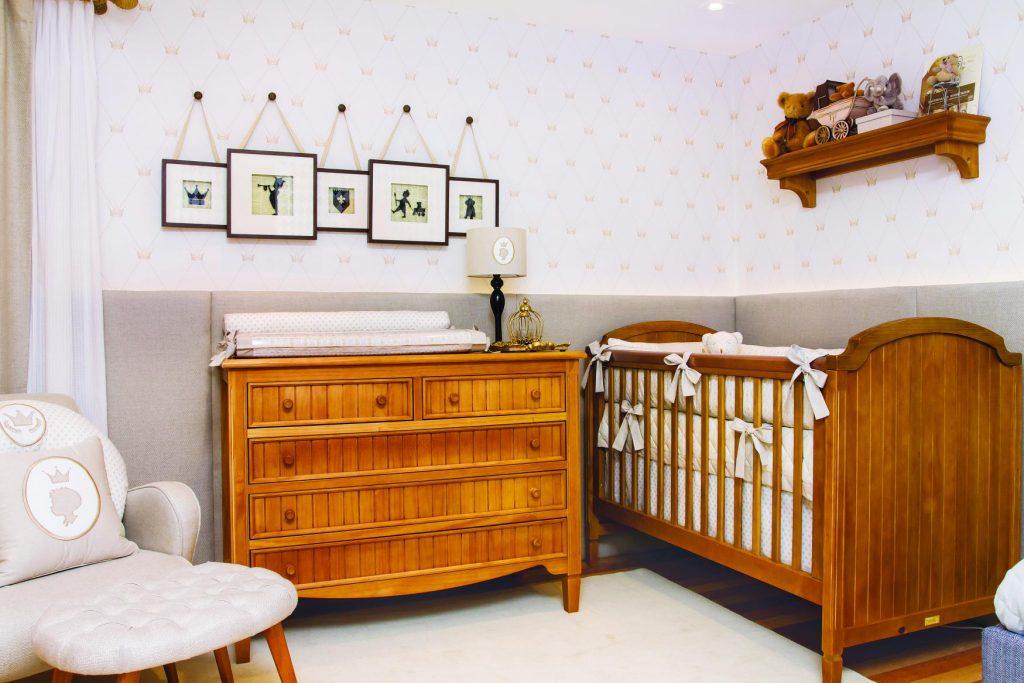 Decorado com temática quarto de príncipe, o ambiente tem bercço, cômoda e prateleira e madeira, poltrona e banco e quadrinhos decorativos, além de papel de parede e cortinas.