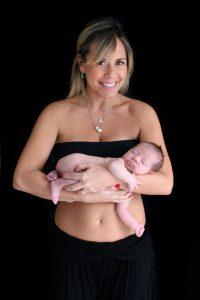 Book gestante. Mulher loira segura bebê no colo. Ela está com um top e calça pretos e colares no pescoço. O fundo da foto é preto