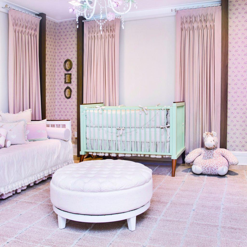 Quarto-verde malva e rosa-antigo elegante com papel de parede floral, três cortinas rosa-antigo, três espelhos pequenos com molduras ovais e retangulares no canto da parede. Do lado esquero, cama babá branca com colcha branca e almofadas coloridas. Ao lado, berço quadrado na cor verde-malva e ao lado uma pelúcia de girafa. Ao centro, pufe com assento capitonado.