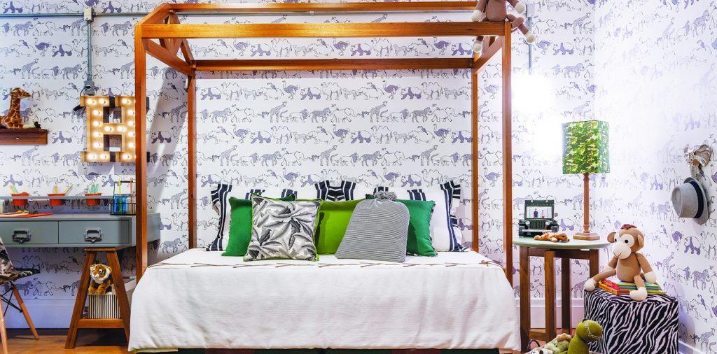 Quarto com cartela de cores escura, papel de parede com estampa de bichos. Cama montessoriana de madeira com almofadas coloridas, ursinhos de pelúcia e pufes com tema safári. Na parede, uma letra H com lâmpadas.