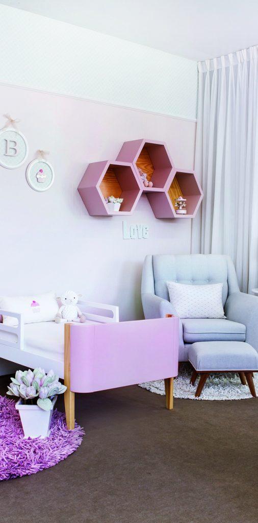 Quarto candy colors com nichos ocagonais rosas, poltrona de amamentação azul e cama babá rosa
