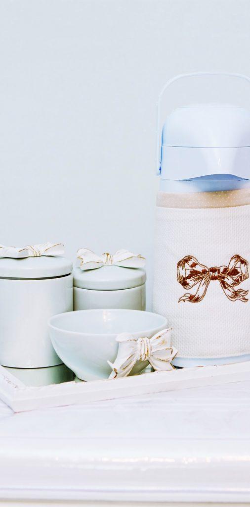 Kit de higiene composto por térmica, molheira e dois potes brancos. Todos têm laço rosa
