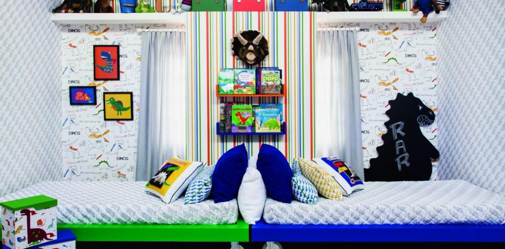 Quarto tema dinossauro com papel de parede branco e cinza com formas geométricas. Quadros com dinossauros na parede. Uma cama verde e uma cama azul, colocadas uma de costas para a outra. Parede do meio tem painel de listras coloridas e prateleiras com brinquedos