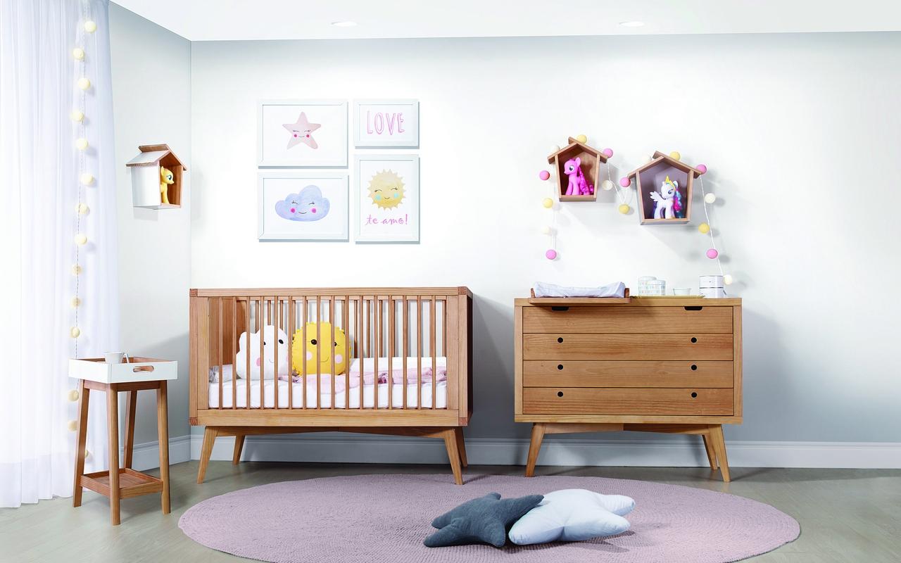 Quarto com parede branca, quadros brancos com desenhos coloridos, berço e cômoda de madeira, um banquinho, tapete rosa com almofadas de estrelas e nichos na parede com ursinhos