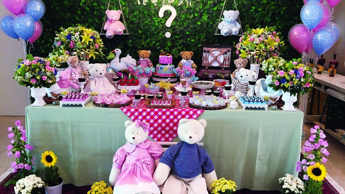 Chá revelação com tema piquenique, com painel de folhas ao fundo com um ponto de interrogação, bexigas azusis e rosas. Mesa com toalha xadrez vermelha, bolo fake azul e rosa, doces e diveros ursinhos com roupas rosas e azuis.