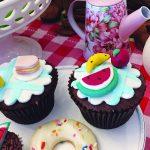 Chá com tema piquenique com cupcakes cobertos com miniaturas de melancia, banana e mini donuts.