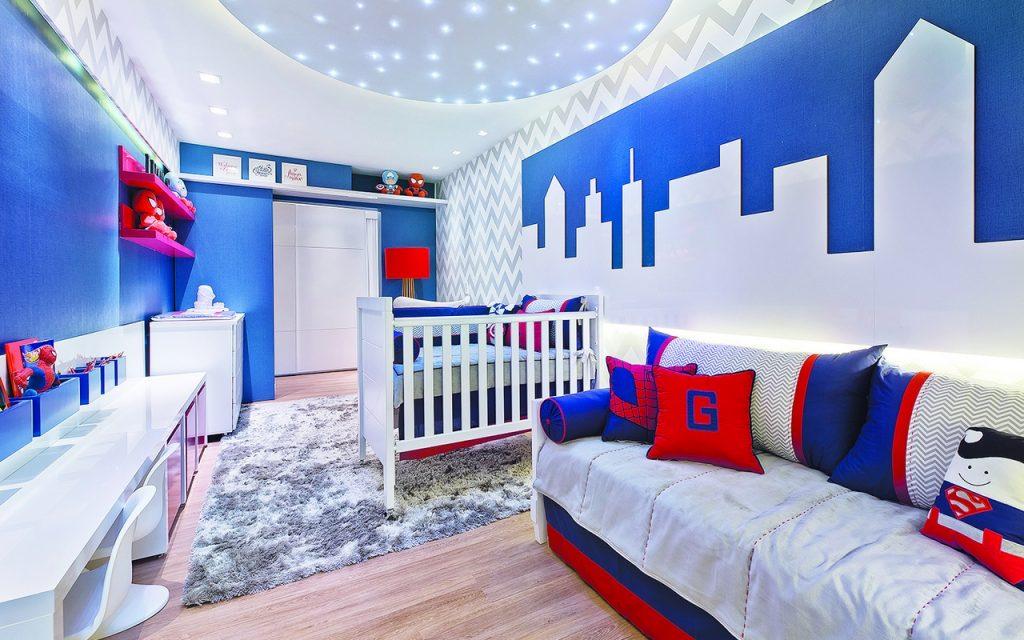 Quarto azul e vermelho com paredes azusi, porta branca, berço branco, cama branca com lençois brancos e almofadas azuis e vermelhas. Escrivaninha branca com detalhes vermelhos e cachepôs com super herois de pelúcia. Na parede, desenhos de prédios. Abajur vermelho, cômoda branca com kit de higiene em cima e prateleiras vermelhas com pelúcias do homem aranha.