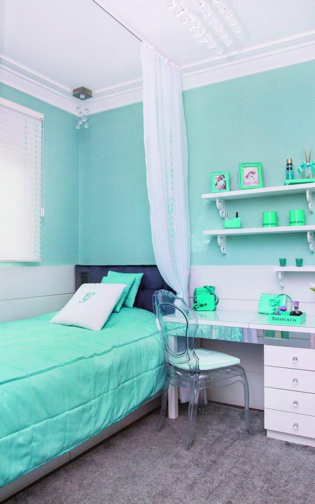 Quarto azul tiffany com parede azul, cama cinza com colcha azul tiffany, cadeira transparente, mesa espelhada com gavetas brancas, dossel de voal branco e prateleira branca com quadros