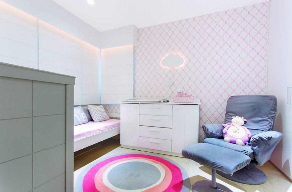 Quarto com móveis neutros, berço com ursinha rosa, papel de parede geométrico com listras rosas
