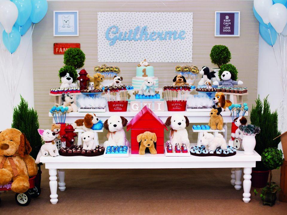 Festa tema cachorrinho, com mesa branca, casinha de cachorro vermelha com cachorro de pelúcia dentro, bolo e doces coloridos e quadro na parede com o nome Guilherme escrito